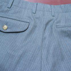 右ききの方は、左側のパンツポケットを使用することが多いことから、パンツの後ろポケットは左側を釦止めとしたり、フタを付けて釦止めとすることが多いです。また、ポケットフタの形をベロやループ、ベース型などに変形も可。用心のために左右とも釦止めとしたり、フタ付き釦止めも選べます。