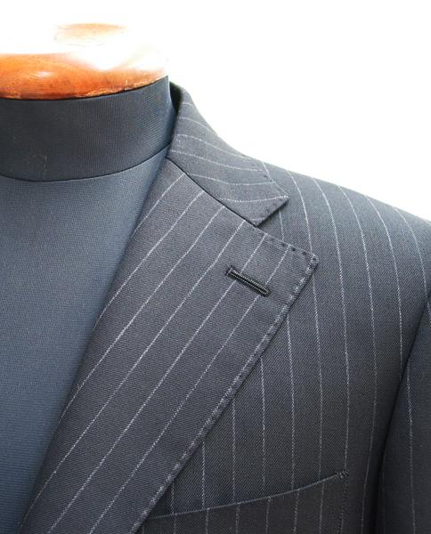 シングル3釦段返りで仕立てた1.2cm巾程度のストライプ・ダークスーツ。 クラシコスーツに特徴的な広めのラペル巾に(…)