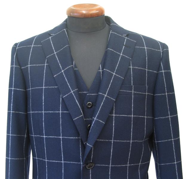 この秋冬シーズンに注目の紡毛系服地とチェック柄で 仕立てたカノニコ・スリーピーススーツ。(…)