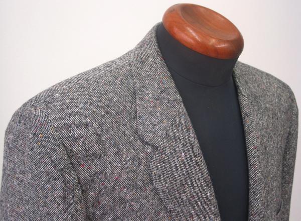 グレーホームスパンのツイード生地を、肩点といわれるショルダー ポイントを一般のジャケットよりも少し外側に置くことで、(…)